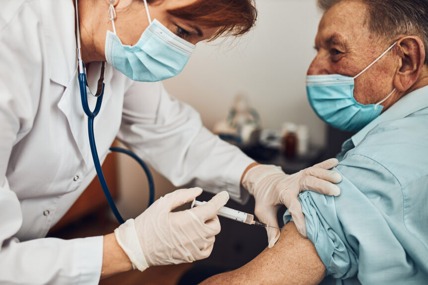 Doctor holding syringe with vaccine and making injection to senior patient with medical mask. Covid-19 or coronavirus vaccine. Physician wearing white coat and gloves using face mask